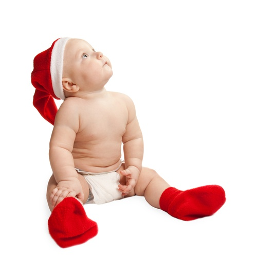 Baby looking up wearing Christmas hat